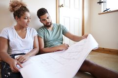 Couple Sitting On Floor Looking At Plans In Empty Room Of New Home stock photography
