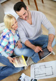 Couple sitting on floor looking at tablet to choose colors walls Royalty Free Stock Image