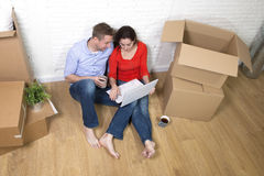 Couple sitting on floor moving in a new house or apartment flat using computer laptop Royalty Free Stock Photos