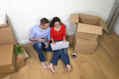 Couple sitting on floor moving in a new house or apartment flat using computer laptop Stock Photo