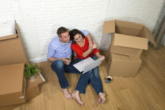 Couple sitting on floor moving in a new house or apartment flat using computer laptop Royalty Free Stock Photography