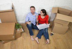 Couple sitting on floor moving in a new house or apartment flat using computer laptop Royalty Free Stock Photo