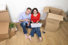 Couple sitting on floor moving in a new house or apartment flat Stock Photo