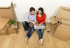 Couple sitting on floor moving in new house choosing furniture with computer laptop. Young happy American couple sitting on floor moving in a new house or Royalty Free Stock Photos