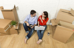 couple sitting on floor moving in new house choosing furniture with computer laptop Royalty Free Stock Photography