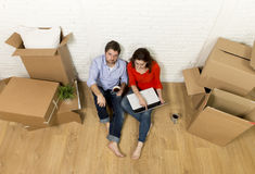 couple sitting on floor moving in new house choosing furniture with computer laptop Stock Photography