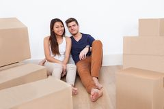 Couple sitting on floor at new home Stock Image