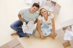 Couple sitting on floor by open boxes in new home royalty free stock images