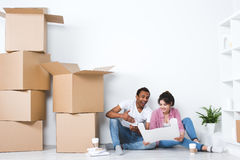 Couple sitting on the floor plans and the scenery in the new house. After moving royalty free stock photo