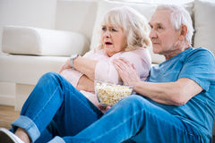 Couple sitting on floor with popcorn and watching tv, frightened woman. Royalty Free Stock Photos