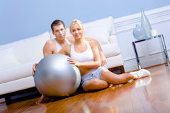 Couple Sitting on Floor With Silver Exercise Ball Stock Images
