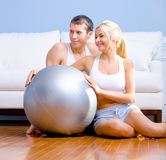 Couple Sitting on Floor With Silver Exercise Ball Royalty Free Stock Photos