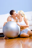 Couple Sitting on Floor With Silver Exercise Ball Stock Image