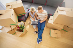 Couple sitting on floor surrounded with moving boxes royalty free stock image