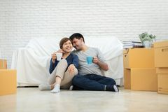Couple sitting on the floor at their new home. Happy Young Couple sitting on the floor at their new home. Moving house day royalty free stock photos
