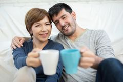 Couple sitting on the floor at their new home. Happy Young Couple holding cups of coffee at their new home. Moving house day royalty free stock image