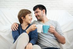 Couple sitting on the floor at their new home. Happy Young Couple holding cups of coffee at their new home. Moving house day. Looking each other stock photo