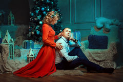 Couple sitting on the floor under Christmas tree. Stock Image