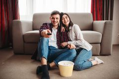 Couple sitting on floor and watch tv with popcorn. Smiling couple sitting on the floor against couch and watch tv with popcorn at home, men with remote control stock photo