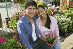 Couple Sitting Among flowers at plant nursery portrait Royalty Free Stock Photos