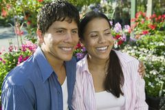 Couple Sitting Among flowers at plant nursery portrait Stock Images