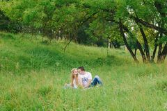 Couple sitting in the forest grass spending time stock images