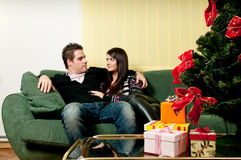 Couple sitting in front of christmas tree Stock Images
