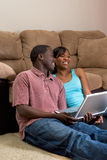 Couple Sitting in front of Couch with Laptop Com Stock Images