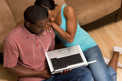 Couple Sitting in front of Couch with Laptop Com Royalty Free Stock Photos