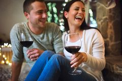 Couple sitting in front of fireplace, drinking wine. Royalty Free Stock Photos