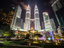 Couple sitting in front of the Petronas Towers and KLCC at Christmas Time. The Petronas Towers and Suria KLCC at Christmas at dusk Royalty Free Stock Images