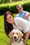 Couple sitting with golden retriever in park Stock Images
