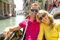 Couple sitting in gondola and smiling. Couple with sunglasses sitting in gondola and smiling stock images