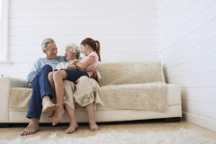 Couple Sitting With Granddaughter On Couch Royalty Free Stock Photo