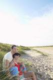Couple Sitting In Grass On Beach Royalty Free Stock Images