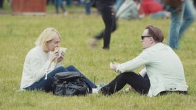 Couple sitting on grass eating burgers at crowded summer city festival in park stock video