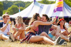 Couple sitting on the grass embracing at a music festival Stock Photos