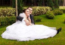 Couple sitting on grass in park and hugging Royalty Free Stock Photography
