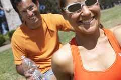 Couple sitting on grass in park, smiling, man holding water bottle, close-up, portrait (tilt). Couple sitting on grass in park, smiling, men holding water bottle Stock Photos