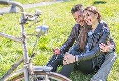 Couple sitting on the grass and relaxing stock photo