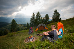 Couple sitting on the green grass near campfire, tents, backpacks Stock Image