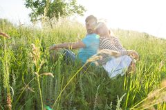 Couple sitting on green grass in the sun shine ray. Man and woman on ground in grass looking each other over shoulders royalty free stock image