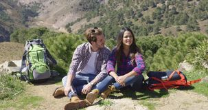 Couple sitting on ground in mountains. Laughing couple having rest and sitting on ground with mountains in summer time on background stock video footage