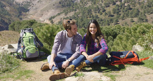 Couple sitting on ground in mountains Royalty Free Stock Photos
