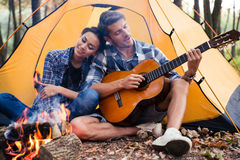 Couple sitting with guitar near bonfire. Portrait of a happy couple sitting with guitar near bonfire in the forest royalty free stock images