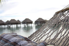 Couple sitting on Hammock looking over the beach and overwater huts Royalty Free Stock Photo