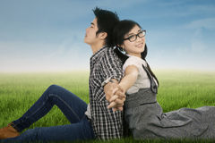 Couple sitting and holding hands on park Stock Images