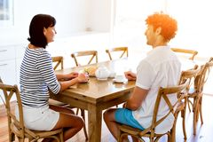 Couple sitting at home and chatting. Couple sitting at home in the kitchen and chatting stock photos