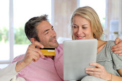 Couple sitting at home and shopping online with tablet Stock Photos