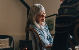 Couple sitting at home talking to each other. Old woman laughing while having a conversation with a person at home. Couple sitting at home talking to each other stock image